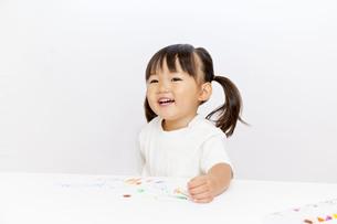 クレヨンで絵を描きながら微笑む幼い女の子の写真素材 [FYI01187478]