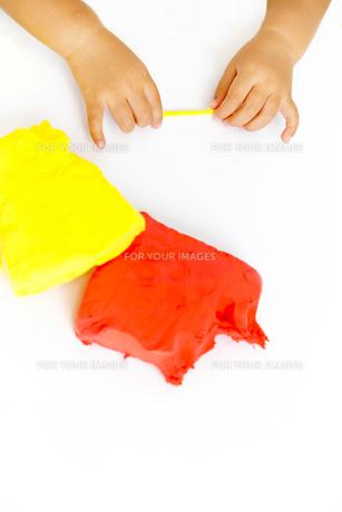 粘土で遊ぶ幼い女の子女の子の手元の写真素材 [FYI01187738]