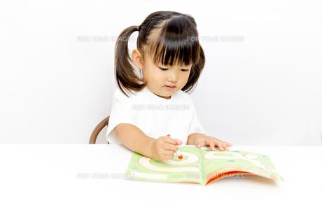 絵本で1人学習する幼い女の子の写真素材 [FYI01187742]
