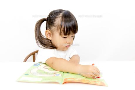 絵本で1人学習する幼い女の子の写真素材 [FYI01187744]