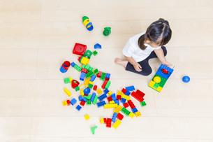 カラフルなブロックで1人遊ぶ幼い女の子の俯瞰の写真素材 [FYI01187748]