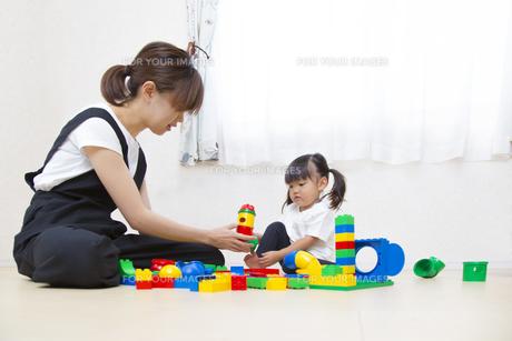 カラフルなブロックでお母さん一緒に遊ぶ幼い女の子の写真素材 [FYI01187749]