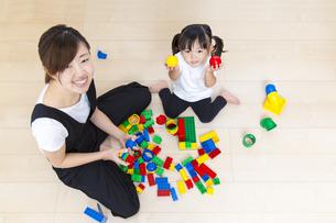 カラフルなブロックでお母さん一緒に遊ぶ幼い女の子の俯瞰の写真素材 [FYI01187750]
