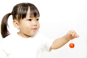 サクランボを1個持つ幼い女の子の横顔の写真素材 [FYI01187756]