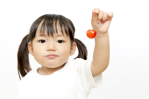 サクランボを1個持つカメラ目線の幼い女の子の写真素材 [FYI01187757]