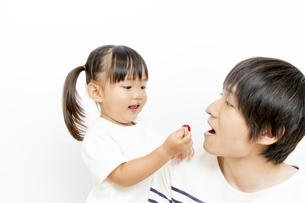 サクランボをお父さんに上げる幼い女の子の写真素材 [FYI01187759]