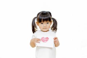 ハートを描いた手紙を渡す胸に持つ幼い女の子の写真素材 [FYI01187768]