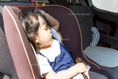 夏の炎天下の中、チャイルドシートで1人寝る幼児のイメージの写真素材 [FYI01187937]