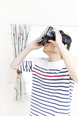 VRゴーグルで仮想現実を自宅で楽しむ男性の写真素材 [FYI01187939]