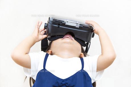 VRゴーグルで仮想現実を楽しむ幼い女の子の写真素材 [FYI01187940]