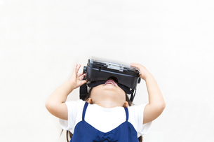 VRゴーグルで仮想現実を楽しむ幼い女の子の写真素材 [FYI01187941]