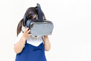 VRゴーグルで仮想現実を楽しむ幼い女の子の写真素材 [FYI01187942]