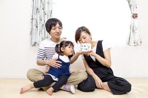 手の平に模型の家を見つめ、計算する夫婦イメージの写真素材 [FYI01187943]