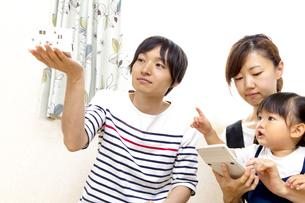 手の平に模型の家を見つめ、計算する夫婦イメージの写真素材 [FYI01187946]