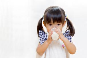 コップでミルクを飲む幼い女の子の写真素材 [FYI01187957]