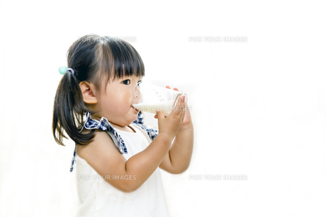 コップでミルクを飲む幼い女の子の写真素材 [FYI01187958]