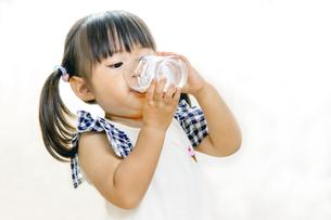 コップでミルクを飲む幼い女の子の写真素材 [FYI01187960]
