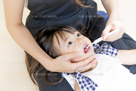 母に歯を磨いてもらう幼い女の子の写真素材 [FYI01187977]