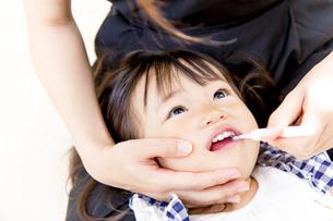 母に歯を磨いてもらう幼い女の子の写真素材 [FYI01187978]