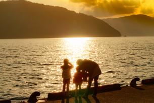 湖の夕焼けと親子の写真素材 [FYI01188190]