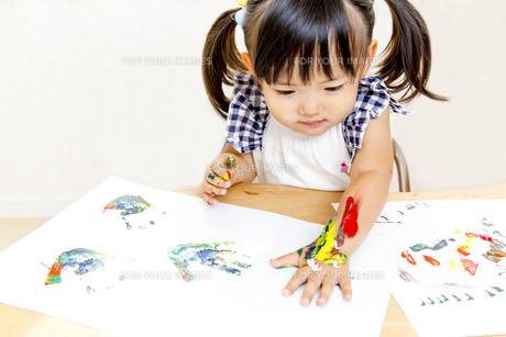 絵具で手形を付けて遊ぶ幼い女の子の写真素材 [FYI01188462]