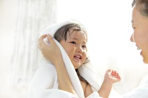 湯上りにお母さんに髪を拭いてもらう幼い女の子の写真素材 [FYI01188471]