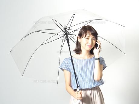 傘をさしながら電話をする若い女性の写真素材 [FYI01188625]
