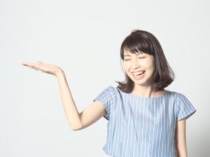 手のひらを上にして笑う若い女性の写真素材 [FYI01188742]
