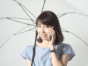 雨傘をさしながらスマホを使う若い女性の写真素材 [FYI01188746]