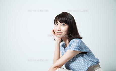 しゃがんでポーズする若い女性の写真素材 [FYI01188771]