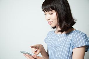 スマートフォンを操作する若い女性の写真素材 [FYI01188787]