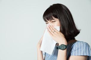ティッシュで鼻をかむ若い女性の写真素材 [FYI01188795]