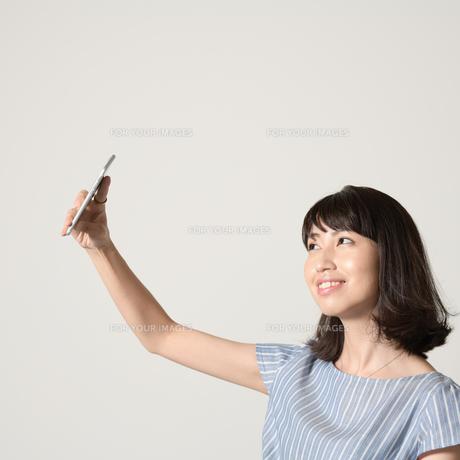 スマートフォンで自撮りする女性の写真素材 [FYI01188892]