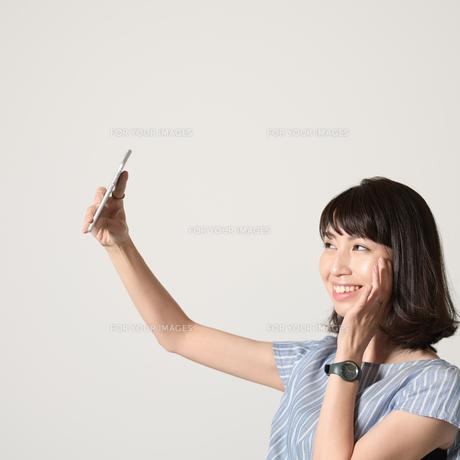 スマートフォンで自撮りする女性の写真素材 [FYI01188893]