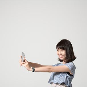 スマートフォンで自撮りする女性の写真素材 [FYI01188894]