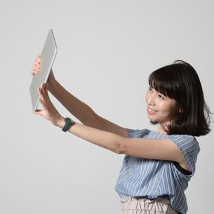 タブレットで自撮りする女性の写真素材 [FYI01188895]