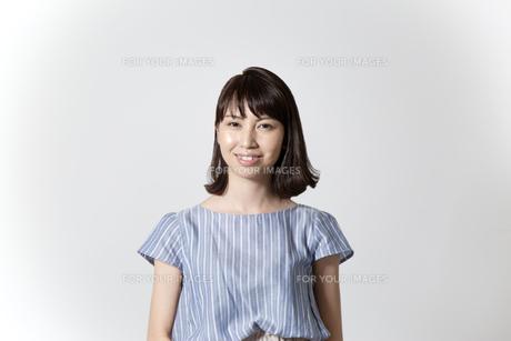 ウエストアップ、正面向きで微笑む若い女性の写真素材 [FYI01188944]