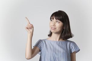 左上へ指差しをする、指差し方向目線の若い女性の写真素材 [FYI01188945]