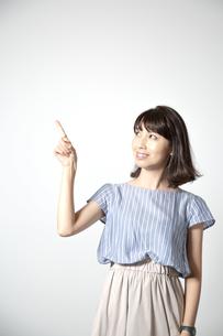 左上へ指差しをするカメラ目線の若い女性の写真素材 [FYI01188948]