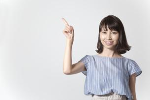左上へ指差しをするカメラ目線の若い女性の写真素材 [FYI01188949]