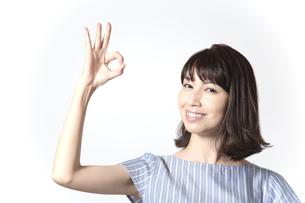 OKサインをするカメラ目線の若い女性の笑顔の写真素材 [FYI01188953]