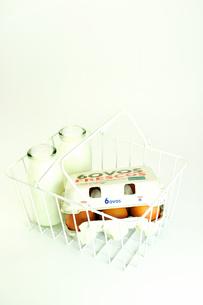 スチール製のカゴに入った牛乳と紙パック入りの卵の写真素材 [FYI01189054]