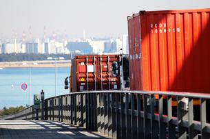 海にかかる橋の上を渡るコンテナ輸送トラックの写真素材 [FYI01189729]