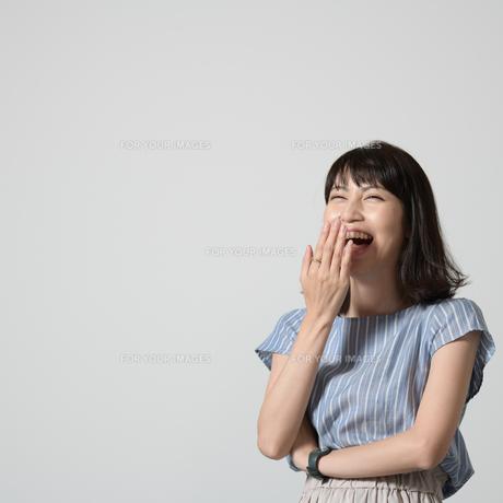 手を口に当てて笑う女性の写真素材 [FYI01189851]