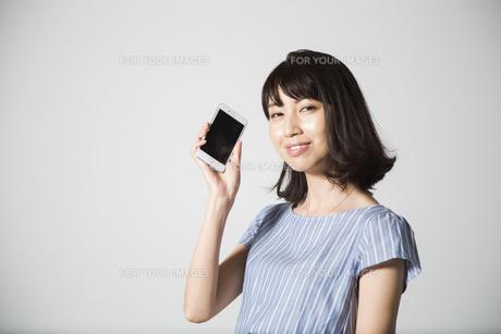 携帯電話で話す若い女性の写真素材 [FYI01190827]