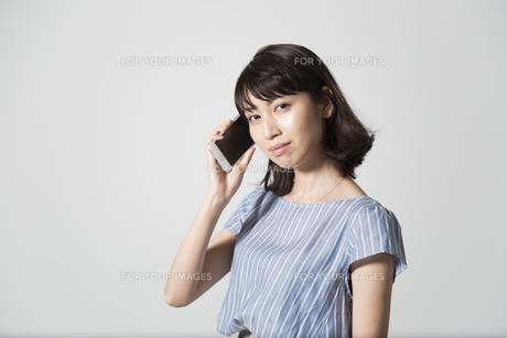 携帯電話で話す若い女性の写真素材 [FYI01190828]