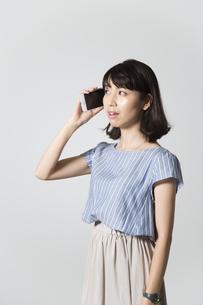 携帯電話で話す若い女性の写真素材 [FYI01190830]