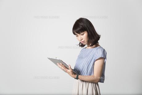 タブレットを操作する若い女性の写真素材 [FYI01190831]
