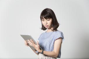タブレットを操作する若い女性の写真素材 [FYI01190834]