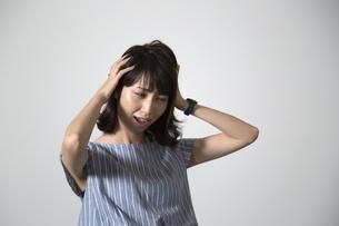 頭を抱える若い女性の写真素材 [FYI01190910]